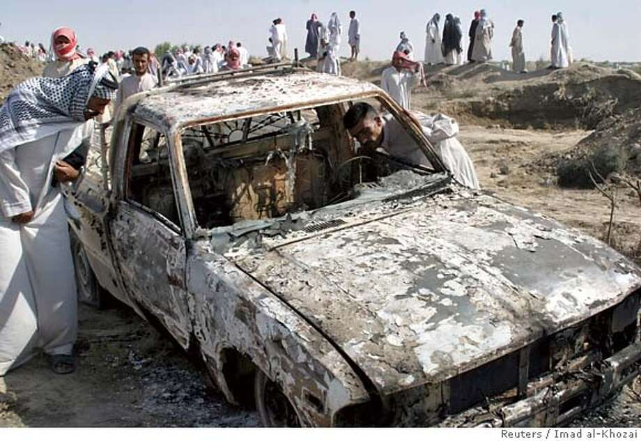 Residents inspect a burnt truck near a crater after an explosion near Diwaniya, 180 km (112 miles) south of Baghdad, August 29, 2006. An explosion killed at least 15 people who were siphoning petrol from pools formed around a breach in a disused fuel pipeline in central Iraq late on Monday, witnesses said on Tuesday. REUTERS/Imad al-Khozai (IRAQ) 0 Photo: IMAD AL KHOZAI