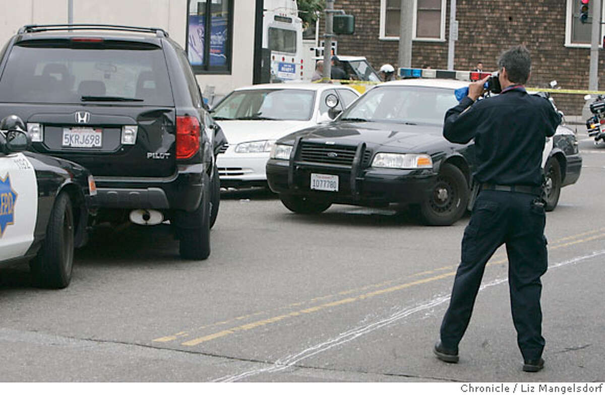 An SFPD officer photographers the suspect's vehicle, which he abandoned, on Spruce Street at California in San Francisco on Aug. 28, 2006. He is suspected in a number of hit and run incidents in San Francisco. Liz Mangelsdorf /The Chronicle