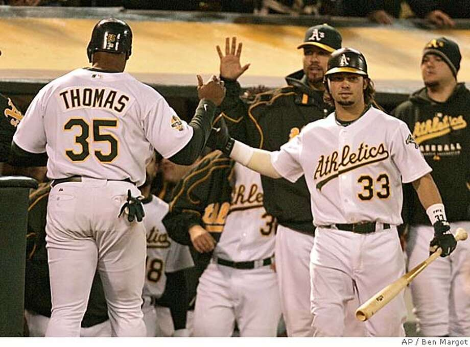 Oakland Athletics' Frank Thomas (35) is welcomed to the dugout by Nick Swisher (33) and others after scoring on a triple by Eric Chavez in the fourth inning of a baseball game against the Boston Red Sox Tuesday, Aug. 29, 2006, in Oakland, Calif. (AP Photo/Ben Margot) Photo: BEN MARGOT