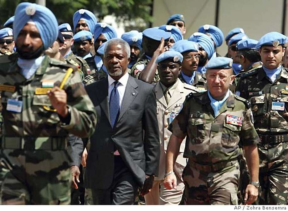 U.N. Secretary-General Kofi Annan, left, is escorted with U.N. French Force Commander Alain Pellegrini, right, upon his arrival in Naqura,the southern headquarters of United Nations Interim Force in Lebanon, or UNIFIL about 5 kilometers (3 miles) from the Israeli border, Tuesday Aug. 29, 2006. Annan on Monday demanded that Hezbollah release two captured Israeli soldiers to the international Red Cross, pressing both sides to fulfill their commitments to solidify the two-week-old cease-fire in Lebanon. (AP Photo/Zohra Bensemra, POOL) POOL PHOTO Photo: ZOHRA BENSEMRA