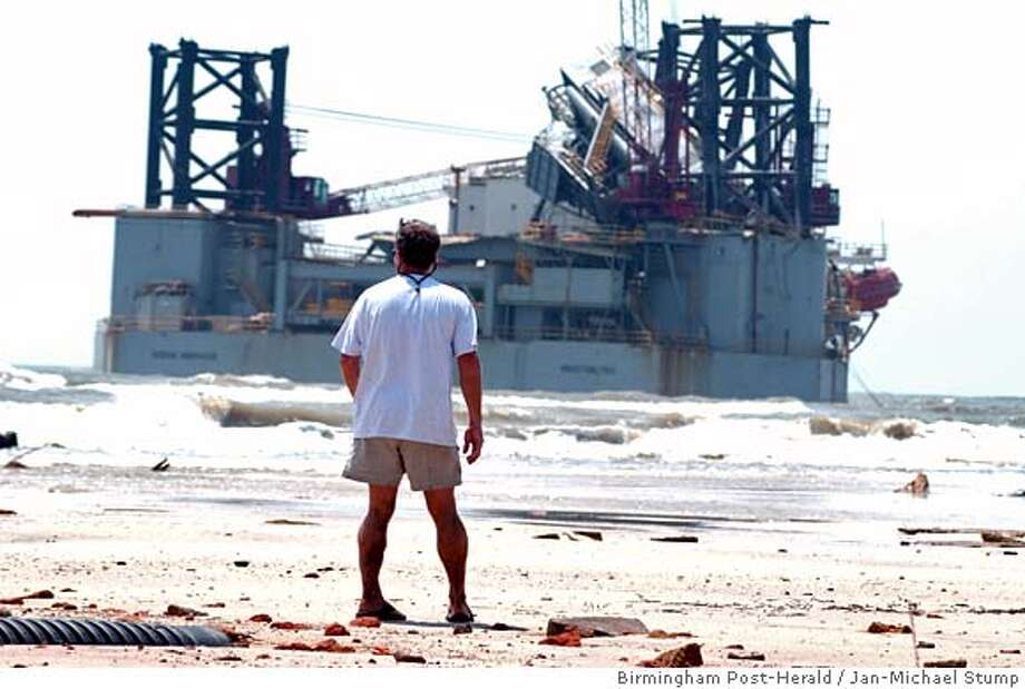 Dennis Knizley looks out on an oil rig beached just off of Dauphin Island, Ala., Tuesday afternoon, Aug. 30, 2005, a day after Hurricane Katrina destroyed much of the island and brought the enormous structure a few hundred yards from shore. (AP Photo/Birmingham Post-Herald, Jan-Michael Stump) Photo: JAN-MICHAEL STUMP