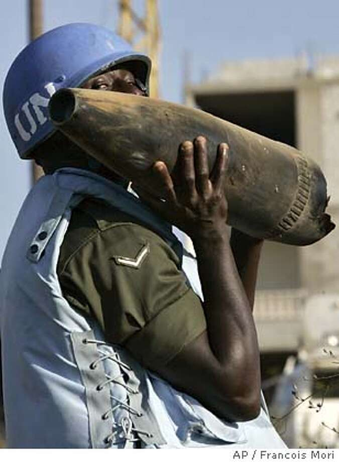 A United Nations peacekeeping engineer from Ghana of the MAG (Mine Advisory Group) holds an used ordnance in Bent Jbail, south Lebanon, Monday Aug. 28, 2006. Unexploded ordnance are dismantled since the end of the month-long Hezbollah-Israel conflict. (AP Photo/Francois Mori) Photo: FRANCOIS MORI