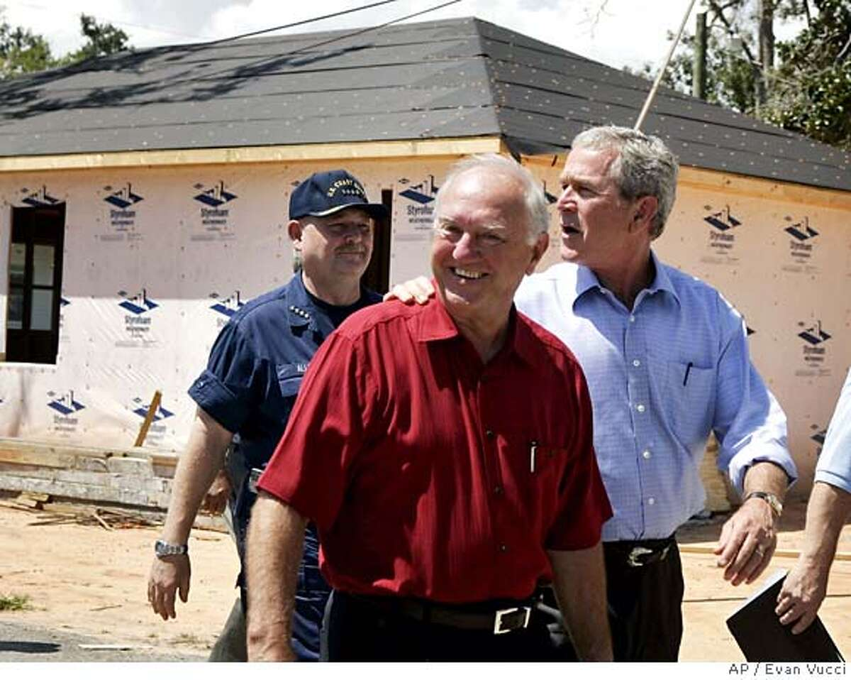 President Bush, right, takes a tour of a neighborhood damaged by Hurricane Katrina with Biloxi Mayor A.J. Holloway, right, on Monday, Aug. 28, 2006 in Biloxi, Miss. Bush suggested Monday that Washington may not be willing to send more than the $110 billion already approved for a Gulf Coast still struggling to come back from Hurricane Katrina's battering, and said a full recovery is likely to take years.(AP Photo/Evan Vucci)