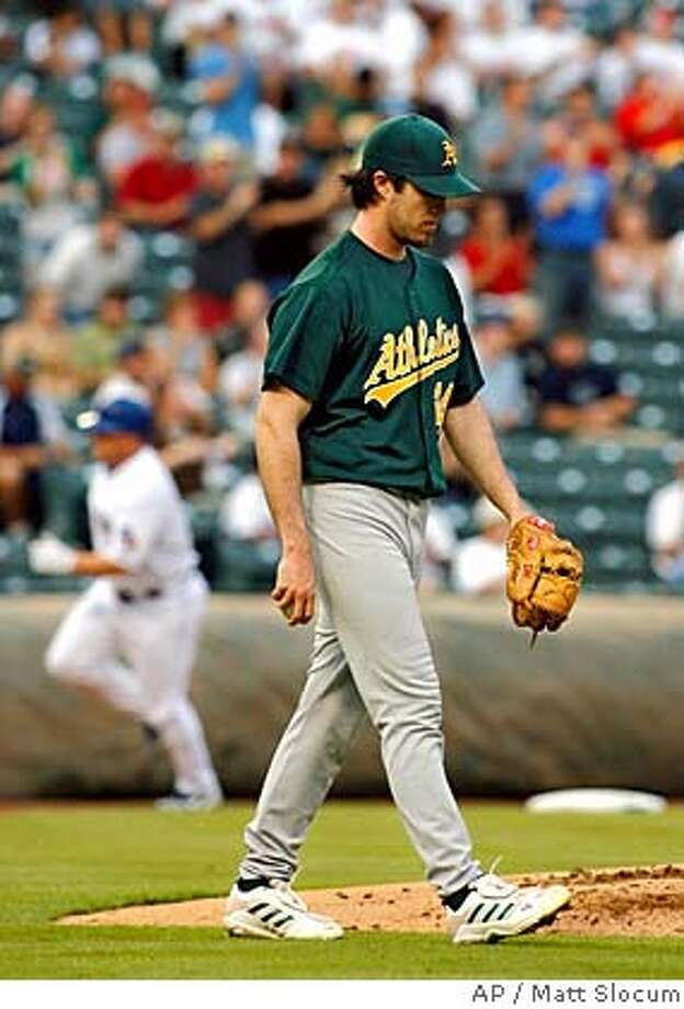 Oakland Athletics pitcher Dan Haren walks back to the mound after giving up a two-run home run to Texas Rangers' Matt Stairs, background left, during the second inning of a MLB baseball game, Sunday, Aug. 27, 2006, in Arlington, Texas. (AP Photo/Matt Slocum) Photo: MATT SLOCUM