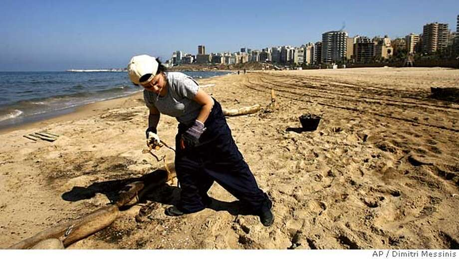 A volunteer from Green Line NGO clean Ramlet-el-Baida beach in Beirut damaged by an oil spill caused by Israeli bombardment during the month-long war on Thursday Aug. 24, 2006. Some 110,000 barrels began pouring into the Mediterranean after Israeli warplanes on July 14 hit a coastal power plant at Jiyeh, 12 miles south of Beirut. More missiles hit a day later. Six fuel tanks ruptured in all, sparking explosions that knocked out a dike meant to prevent spills. (AP Photo/Dimitri Messinis) Photo: DIMITRI MESSINIS