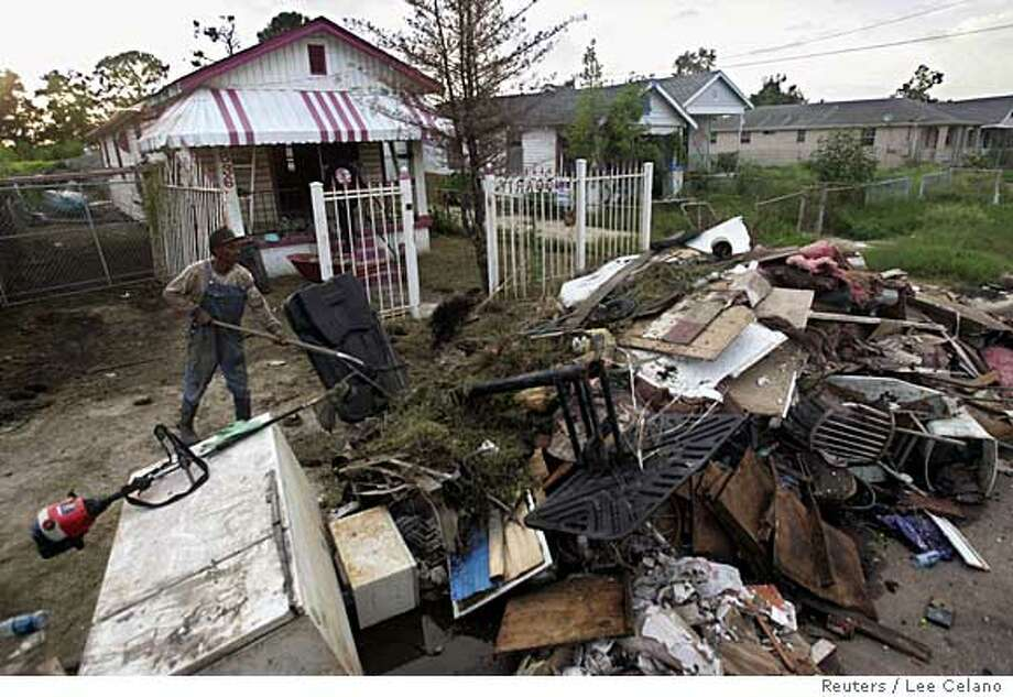 L.C. McCarty clears debris at his son's house that was hit by Hurricane Katrina in the Lower Ninth Ward of New Orleans August 12, 2006. REUTERS/Lee Celano (UNITED STATES)  Ran on: 08-27-2006  Disaster in the Lower Ninth Ward: L.C. McCarthy piles up debris from his son's house nearly a year after Hurricane Katrina devastated New Orleans. Photo: LEE CELANO