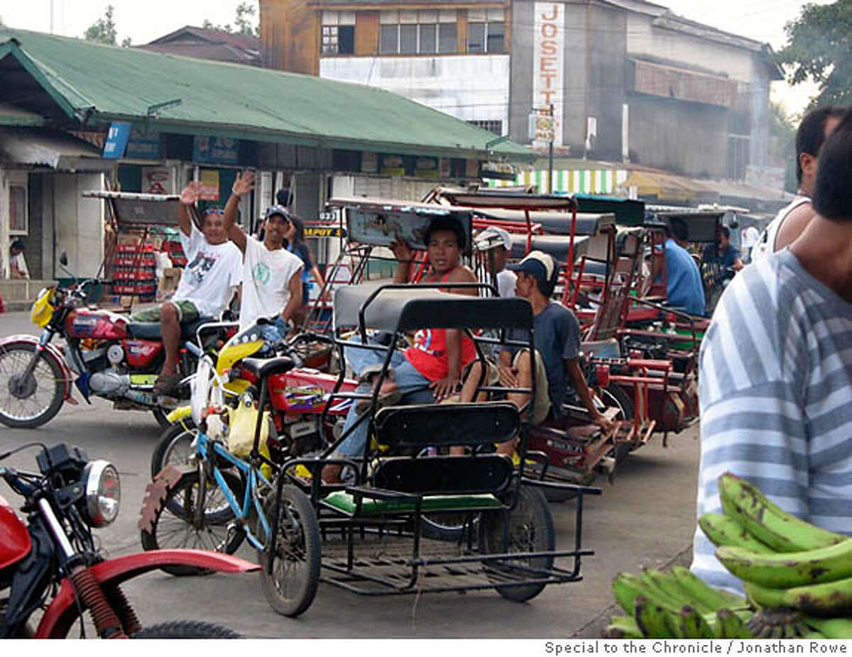 Trisikads waiting outside the public market in the center of La Castellana, Philippines.