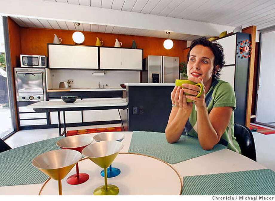 "Monika in her original looking Eichler dinning room and kitchen. Tom Borsellino and his wife Monika Kafka have owned two Eichler houses. When they bought their current Eichler in the Willow Glen neighborhood in San Jose, it was plagued by dry rot and termites. The couple didn't ""whitewash'' the place, but aged the new paneling with a special stain so it would match the existing paneling.� To brighten the space, the family chose lighter, more reflective colors for the ceiling, beams, and floor. The kitchen has the same cabinets and layout it had on the day it was built, although the cabinets have been repainted. Eichler cabinets are typically boxes with sliding doors. Over time, some of sliding doors started sticking and many were remodeled out of existence. Event in, San Jose, Ca, on 8/18/06. Photo by: Michael Macor / San Francisco Chronicle Photo: Michael Macor"