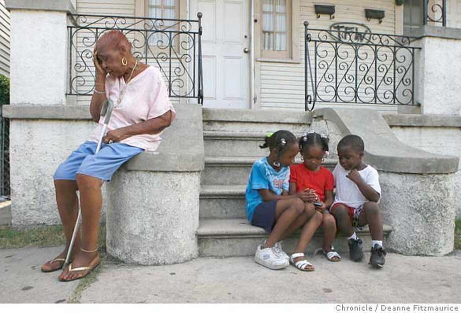 "Rosemary ""Mamma"" Jones cries for no reason since she lost her home and all of her belongings in Katrina. She is sitting on a stairway on her street in the Seventh Ward. The children playing a portable game boy at right are: (l to r) her grandchild, Mychella Peter (cq), 7, her great-grandchild Tia Martin, 4, and her grandchild Miguel Martin, 4. In New Orleans, depression reigns, suicide rate in the area is triple what it was before Katrina, mental hospitals are closed and there are not enough mental health professionals to handle the need for counseling. Photographed in New Orleans on 8/16/06.  (Deanne Fitzmaurice/ The Chronicle) Photo: Deanne Fitzmaurice"
