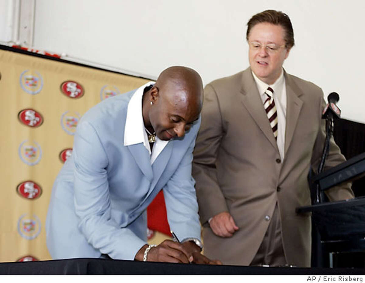 Wide receiver Jerry Rice, left, signs a one-day contract with the San Francisco 49ers as 49ers owner John York, right, looks on during a press conference at the 49ers football headquarters in Santa Clara, Calif., Thursday Aug. 24, 2006.The 49ers will hold an official retirement cereomy for Rice at a game in November.(AP Photo/Eric Risberg)