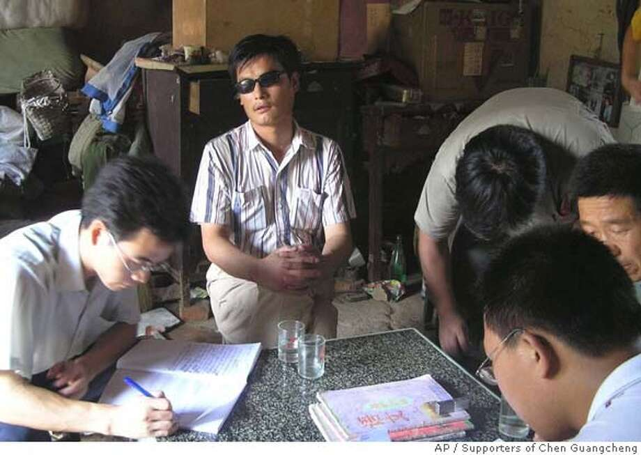 In this undated photo released by supporters of Chen Guangcheng, blind activist Chen Guangcheng, center, is seen in a village in China. Chen is due to go on trial Friday Aug. 18, 2006 in eastern China on criminal charges that his supporters claim were fabricated as retaliation for his activism. Supporters of a blind Chinese activist who documented forced abortions are being kept under house arrest as authorities prepare to put him on trial this week, activists said Thursday, Aug. 17, 2006. (AP Photo/Supporters of Chen Guangcheng, HO) Photo: HO