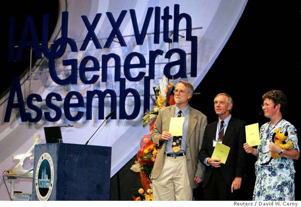 """Members of the International Astronomical Union (IAU) Jocelyne Bell-Burnell (R), Christopher Corbally (C) and Richard Binzel vote during the closing session of IAU's 26th General Assembly in Prague August 24, 2006. Pluto was stripped of its status as a planet on Thursday when astronomers from around the world redefined it as a """"dward planet"""", leaving just eight classical planets in the solar system. REUTERS/David W Cerny (CZECH REPUBLIC)"""