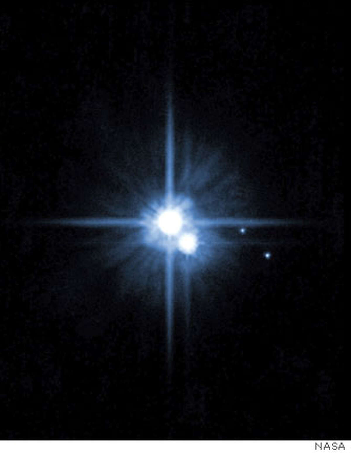 (NYT72) UNDATED -- August 22, 2006 -- Pluto, center, and its three moons in a photograph taken by the Hubble Space Telescope. Under fire from other astronomers and the public, a committee appointed by the International Astronomical Union revised and then revised again a definition proposed last week that would have expanded the number of official planets to 12, locking in Pluto as well as the newly discovered Xena in the outer solar system, as well as the asteroid Ceres and Pluto�s moon Charon. (NASA/The New York Times)