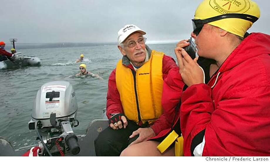 Bob Roper and Allison Kalhammer make a call on a two way radio before the morning sunrise swim for St Francis Yacht Club to the end of Hype Street. Bob Roper is the record holder for the fastest-ever swim across the Golden gate IN 1969. Now 67, he has an artificial valve in his heart, a pacemaker, and needs an operation for a torn rotator cuff. Still, he's in there pitching, encouraging the Sunrisers swim group in the South End Rowing club... and launching for the first time ever the First Annual Invitational Bob Roper Golden Gate Swim (slated for Sept 3). 8/18/06  {Frederic Larson/The Chronicle} MANDATORY CREDIT FOR PHOTOGRAPHER AND SAN FRANCISCO CHRONICLE/ -MAGS OUT Photo: Frederic Larson