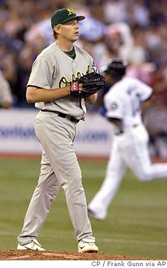 Oakland Athletics starting pitcher Brad Halsey walks back to the mound as Toronto Blue Jays' Vernon Wells rounds the bases on his two run home run during fifth inning AL action in Toronto on Tuesday Aug. 22, 2006. (AP PHOTO/CP, Frank Gunn) Photo: FRANK GUNN