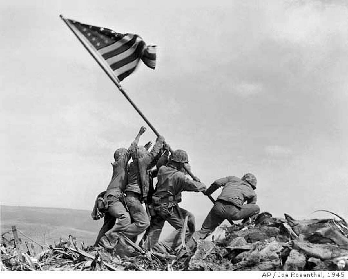 ** FILE ** In a file photo U.S. Marines of the 28th Regiment of the Fifth Division raise the American flag atop Mt. Suribachi, Iwo Jima, on Feb. 23, 1945. Joe Rosenthal, who won a Pulitzer Prize for his immortal image of six World War II servicemen raising an American flag over battle-scarred Iwo Jima, died Sunday. He was 94. (AP Photo/Joe Rosenthal)