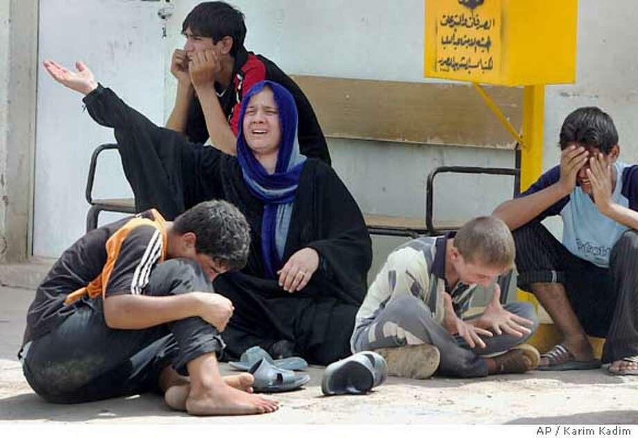 An Iraqi mother along with her children mourn the death of her son Wisam Ali, 13, who was killed on the way to the Imam Moussa Kadhim shrine, for the annual commemoration of the saint's death, at a hospital, in Baghdad, Iraq, Sunday Aug. 20, 2006. Snipers firing from rooftops and a cemetery killed at least 16 people and injured 230 in a series of attacks Sunday on a religious procession in Baghdad by hundreds of thousands of Shiite pilgrims, officials said. Four gunmen were also killed. (AP Photo/Karim Kadim) Photo: KARIM KADIM