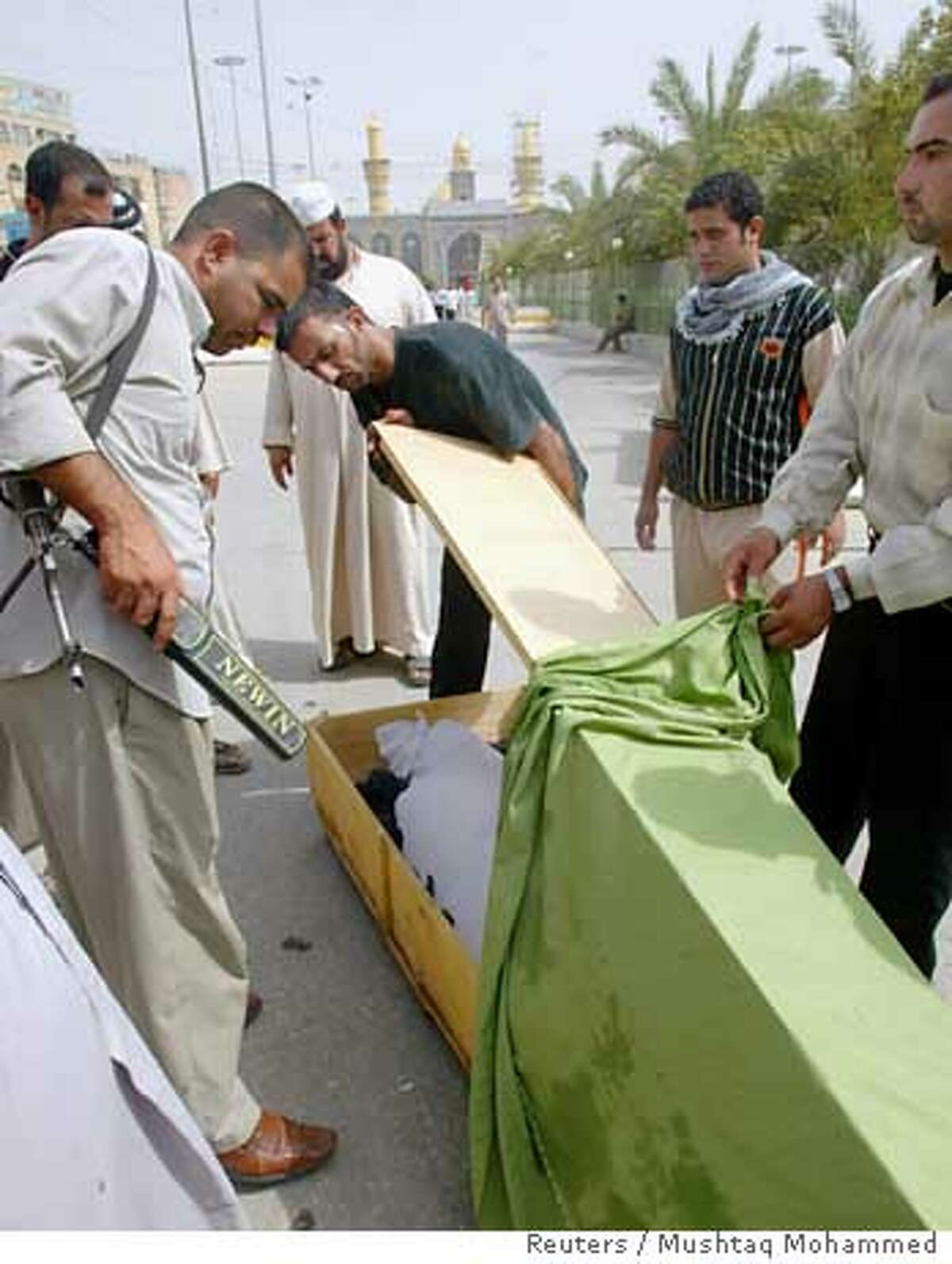 A shrine guard inspects the body of a Shi'ite pilgrim who was among those killed while heading to attend a religious festival in the Khadimiya shrine, during a funeral in Kerbala, 110 km (70 miles) south of Baghdad, August 20, 2006. At least 20 people died and 300 were hurt in Baghdad on Sunday after insurgents, including roof-top snipers, ambushed pilgrims gathering in their hundreds of thousands for a sacred Shi'ite festival. REUTERS/Mushtaq Mohammed (IRAQ)