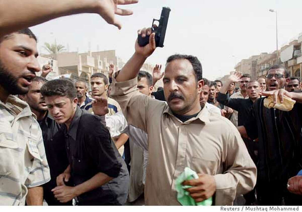 Shi'ite pilgrims wave their pistols while walking outside Imam Abbas shrine as they celebrate a religious festival to mark the death of revered 8th-century imam Musa al-Khadim, in the holy city of Kerbala, 110 km (70 miles) south of Baghdad, August 20, 2006. REUTERS/Mushtaq Mohammed (IRAQ)