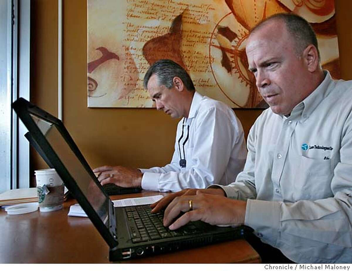 Co-workers Dennis Ortman (left) and Bill Shafer work on their laptops at a Cupertino Starbucks using the free MetroFi to access the internet. Both work for License Technologies Group Inc. and are from Belleview, WA. MetroFi has built and operates Wi-Fi wireless broadband networks in Cupertino, Santa Clara, and Sunnyvale California. Residents and businesses in these cities enjoy high-speed access to the Internet from anywhere in the community - without the use of wires or cables. The service is free, supported by local advertisers and delivers DSL-like speeds (about one megabit per second). Photo by Michael Maloney / San Francisco Chronicle on 8/16/06 in Sunnyvale,CA MANDATORY CREDIT FOR PHOTOG AND SF CHRONICLE/ -MAGS OUT