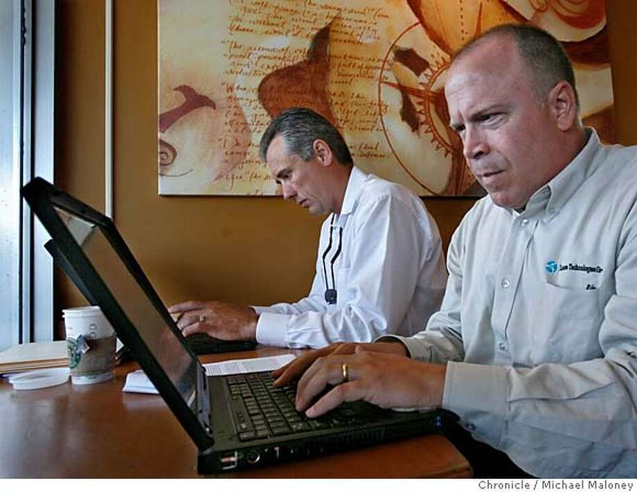 Co-workers Dennis Ortman (left) and Bill Shafer work on their laptops at a Cupertino Starbucks using the free MetroFi to access the internet. Both work for License Technologies Group Inc. and are from Belleview, WA.  MetroFi has built and operates Wi-Fi wireless broadband networks in Cupertino, Santa Clara, and Sunnyvale California. Residents and businesses in these cities enjoy high-speed access to the Internet from anywhere in the community - without the use of wires or cables. The service is free, supported by local advertisers and delivers DSL-like speeds (about one megabit per second).  Photo by Michael Maloney / San Francisco Chronicle on 8/16/06 in Sunnyvale,CA MANDATORY CREDIT FOR PHOTOG AND SF CHRONICLE/ -MAGS OUT Photo: Michael Maloney