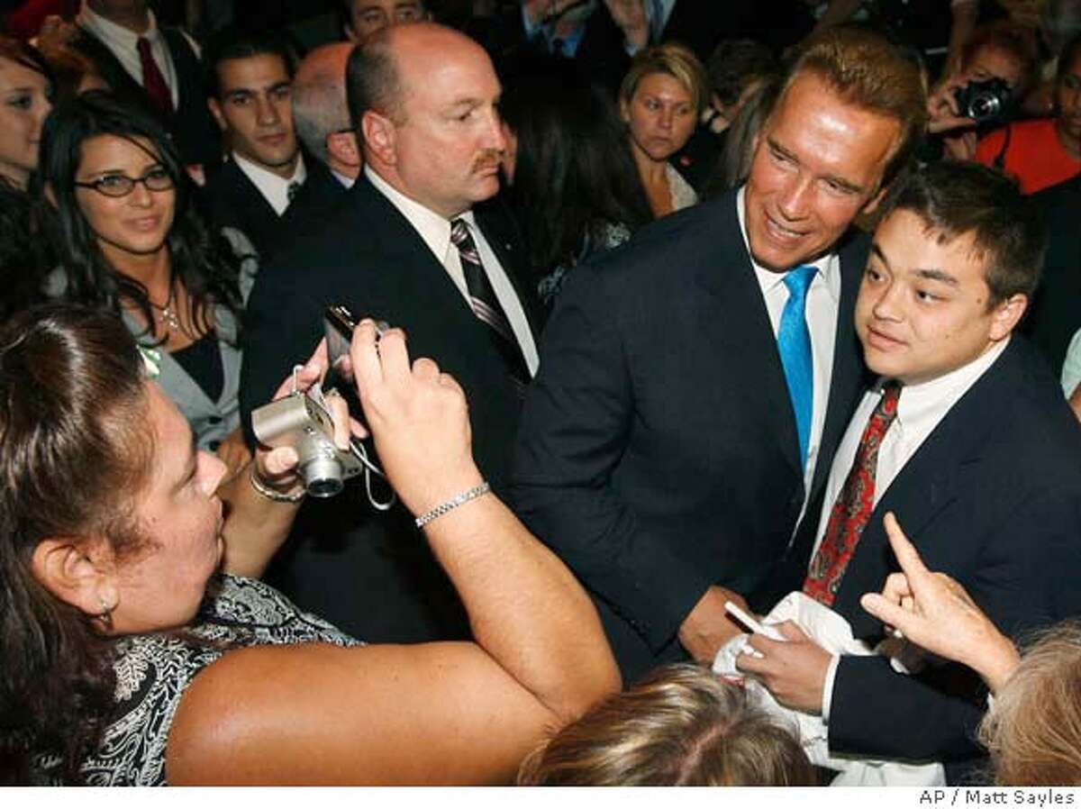 California Gov. Arnold Schwarzenegger takes a picture with a supporter after speaking at California Republican Party state convention in Los Angeles on Saturday, Aug. 19, 2006. (AP Photo/Matt Sayles)