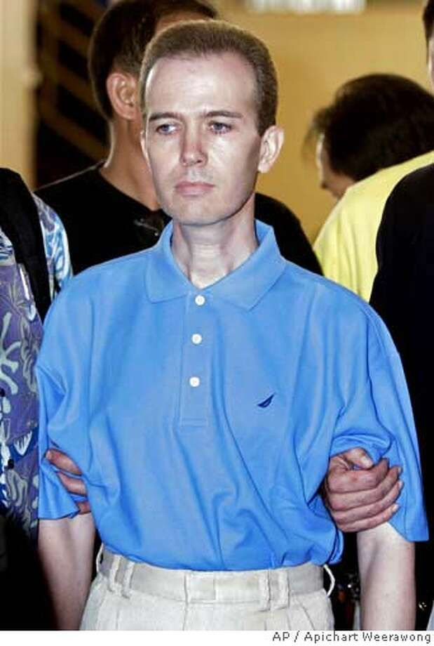 Murder suspect John Mark Karr is led by Thai and U.S. officials from the detention center to a police news conference at Immigration office in Bangkok, Thailand Thursday, Aug. 17, 2006. Karr, 41, an American schoolteacher on Friday, Aug. 18, awaited expulsion to the U.S. where questions mounted over whether his confession to the slaying of 6-year-old beauty queen JonBenet Ramsey was spun from the mind of a kook or a killer. (AP Photo/Apichart Weerawong) THURSDAY, AUG. 17, 2006 PHOTO Photo: APICHART WEERAWONG