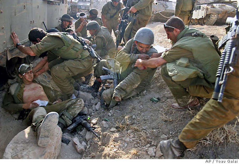 Israeli soldiers from the engineering corps give first aid to wounded colleagues after coming under attack from Hezbollah guerrillas using anti-tank missiles in the village of Inta, outskirts of the southern Lebanon town of Bint Jbail early Saturday Aug. 12, 2006. The unit was clearing routes for armored vehicles and infantry. (AP Photo/Yoav Galai) ** MAGS OUT, TV OUT, NO ARCHIVES, ISRAEL OUT ** MAGS OUT, TV OUT, NO ARCHIVES, ISRAEL OUT - PICTURE MADE AVAILABLE ON TUESDAY AUG. 15, 2006 Photo: YOAV GALAI