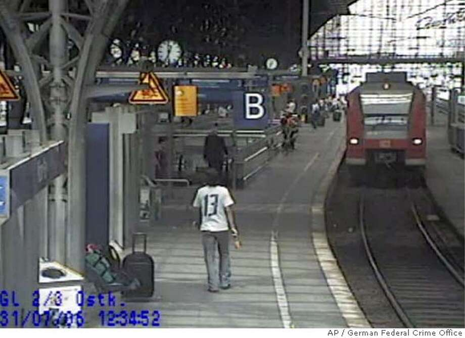 """The picture taken by a surveillance camera released by German Federal Crime Office in Wiesbaden, western Germany, Friday, Aug 18, 2006, shows one of the two men, back to camera in forground, suspected of placing two bombs in two German regional trains on July 31, 2006. German investigators said Friday that two bombs found last month on regional trains had a """"possible terrorist background,"""" but were cautious about drawing conclusions from material with Arabic script found with the devices. The bombs, made with gas canisters, were found July 31 on trains in Dortmund and Koblenz. Joerg Ziercke, the head of Germany's Federal Crime Office, said they apparently were supposed to explode 10 minutes before the trains' arrival at the stations. (AP Photo/German Federal Crime Office) Photo: Federal Criminal Police"""