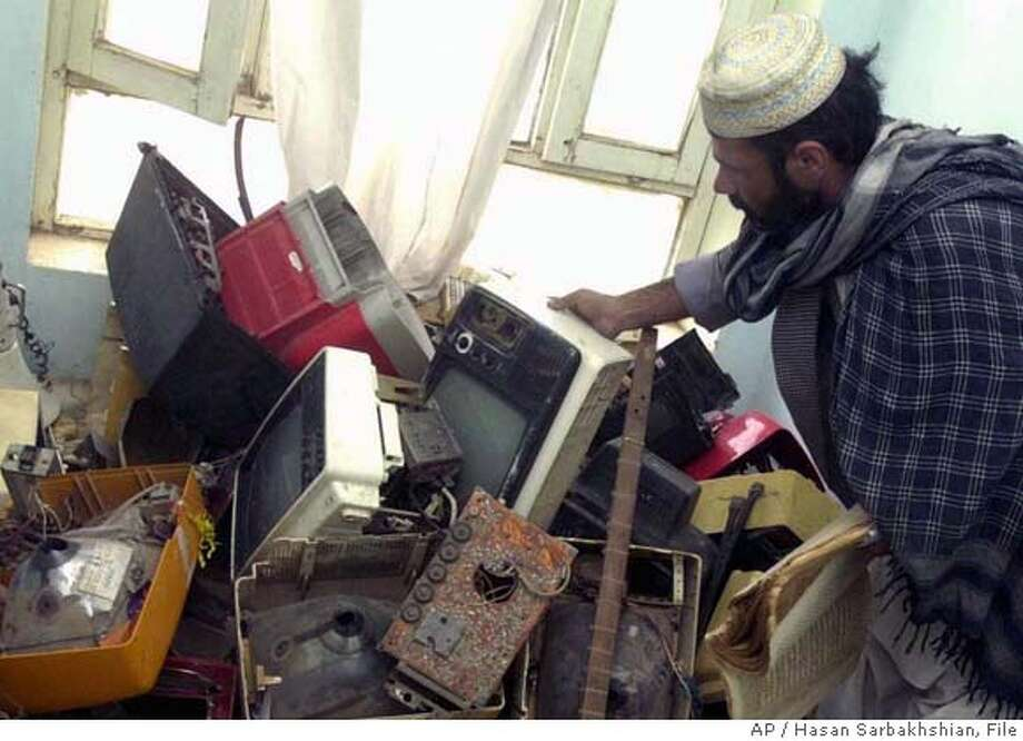 An Afghan man shows television sets that were destroyed by the Taliban at the Ministry for the Promotion of Virtue and Prevention of Vice in Herat, Afghanistan, Saturday, Nov. 24, 2001. Watching television was forbidden under the Taliban rule in Afghanistan. (AP Photo/Hasan Sarbakhshian) DIGITAL IMAGE Photo: HASAN SARBAKHSHIAN