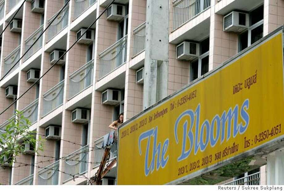 A resident dries his shirt from a balcony of The Blooms apartment in downtown Bangkok August 18, 2006, where primary school teacher John Mark Karr was arrested on Wednesday in connection with the murder of child beauty queen JonBenet Ramsey in 1996. Thai authorities hope to deport Karr to the United States this weekend, officials said on Friday, as questions surfaced over the schoolteacher's story. REUTERS/Sukree Sukplang (THAILAND) Photo: SUKREE SUKPLANG