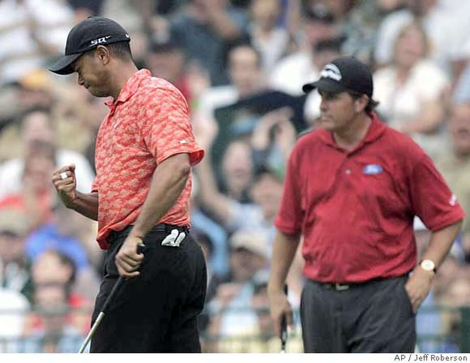 Phil Mickelson, right, watches as Tiger Woods celebrates a birdie on the 18th green during the second round of the PGA Championship golf tournament at Medinah Country Club, Friday, Aug. 18, 2006, in Medinah, Ill. (AP Photo/Jeff Roberson) Photo: JEFF ROBERSON