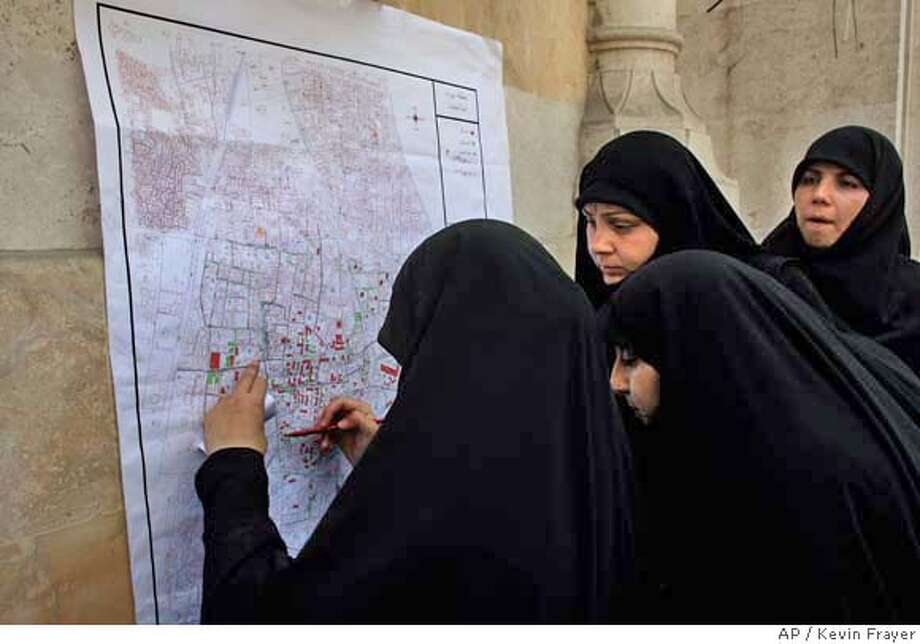 Female Lebanese Hezbollah volunteers look at a map showing areas of destruction as they prepare to help clean-up operations in the Haret Hreik area of the southern suburbs of Beirut, Friday, Aug. 18, 2006. (AP Photo/Kevin Frayer) Photo: KEVIN FRAYER