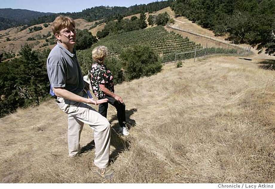 Robert Weems and Diana Dougherty look over the vineyards of David Mease, Thursday Aug. 10,2006, in Nicasio, Ca. They have been riding their horses along Dickson Ridge Trail for years and now is having to fight to keep the trail as it is. The decades-old fire road overlooking the beautiful San Geronimo Valley is known by some as the Dickson Ridge trail and by others as the Mount Barnaby trail. It has been used by equestrians, hikers and bikers for decades. And, like many trails around the Bay Area, it goes right through private property. The landowners David and Catherine Mease want to build their dream home next to a vineyard and they are refusing to grant an easement acknowledging the right of the public to pass through their land on the fire road. This refusal has turned the quarter mile section into a battle ground, pitting the property owners against virtually everybody else. Bikers, hikers and equestrians believe they have an implied right to use the trail because it has been in use for so many decades. They are threatening to sue. Meanwhile, ugly confrontations have occurred on the fire road, which runs across Nicasio�s Moon Hill and connects to a trail network that extends to the Pacific Ocean. It is the kind of battle that is erupting all across the state as property values go up and many owners no longer have the relaxed attitude about public access that rural residents once had, Aug.10,2006, in . (Lacy Atkins/The Chronicle) Ran on: 08-19-2006  Robert Weems and Diana Dougherty look over the vineyard of David Mease and Catherine Salah, near the disputed trail. Photo: Lacy Atkins