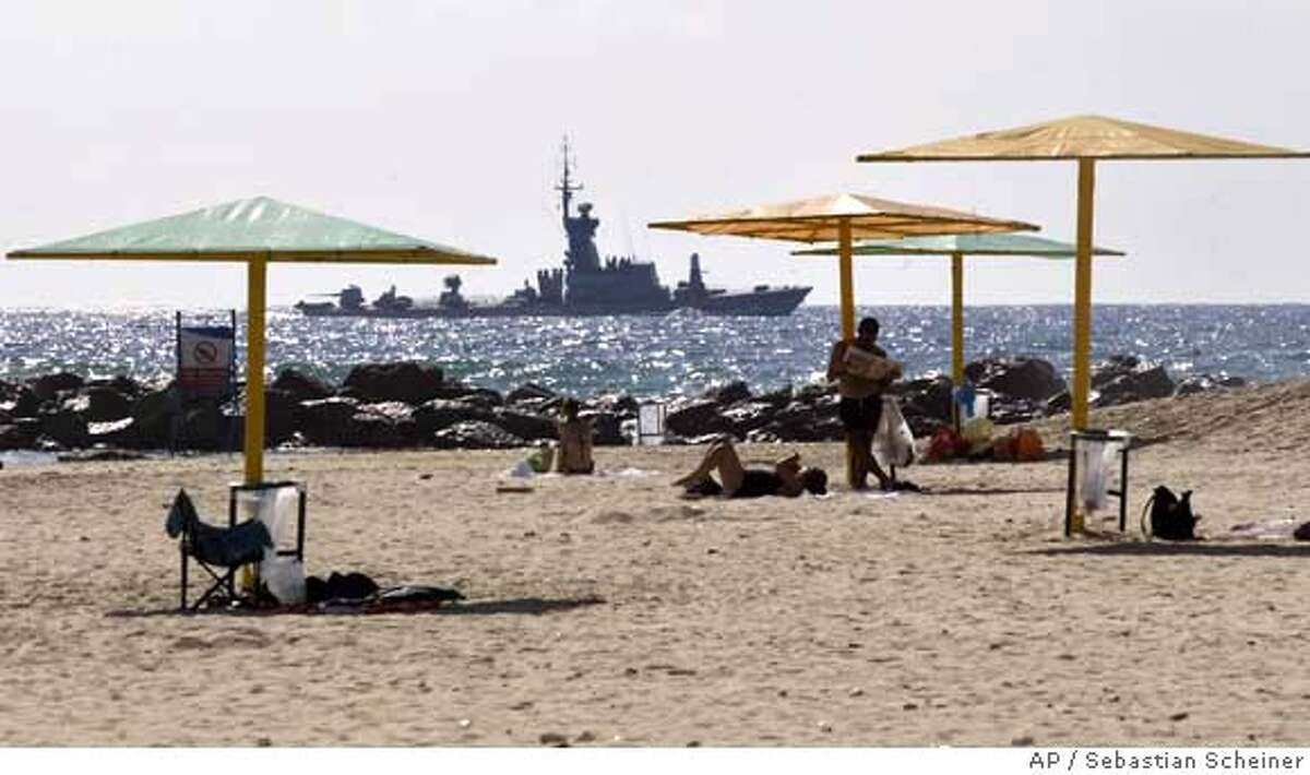 An Israeli military ship sails off the shore of the city of Haifa, northern Israel, as Israeli bathers enjoy the beach Monday Aug. 14, 2006. A U.N.-imposed ceasefire went into effect Monday designed to end a month of violence that killed more than 900 people.(AP Photo/Sebastian Scheiner)