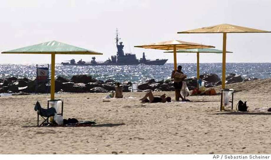 An Israeli military ship sails off the shore of the city of Haifa, northern Israel, as Israeli bathers enjoy the beach Monday Aug. 14, 2006. A U.N.-imposed ceasefire went into effect Monday designed to end a month of violence that killed more than 900 people.(AP Photo/Sebastian Scheiner) Photo: SEBASTIAN SCHEINER