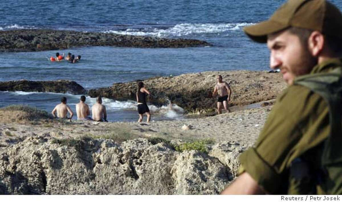 An Israeli soldier mans a guard post, as Israelis (background) enjoy the beach, near the city of Nahariya August 15, 2006. Israeli forces began leaving parts of south Lebanon on Tuesday as a U.N. truce largely held for a second day and the Lebanese army prepared to move south. REUTERS/Petr Josek (ISRAEL) 0