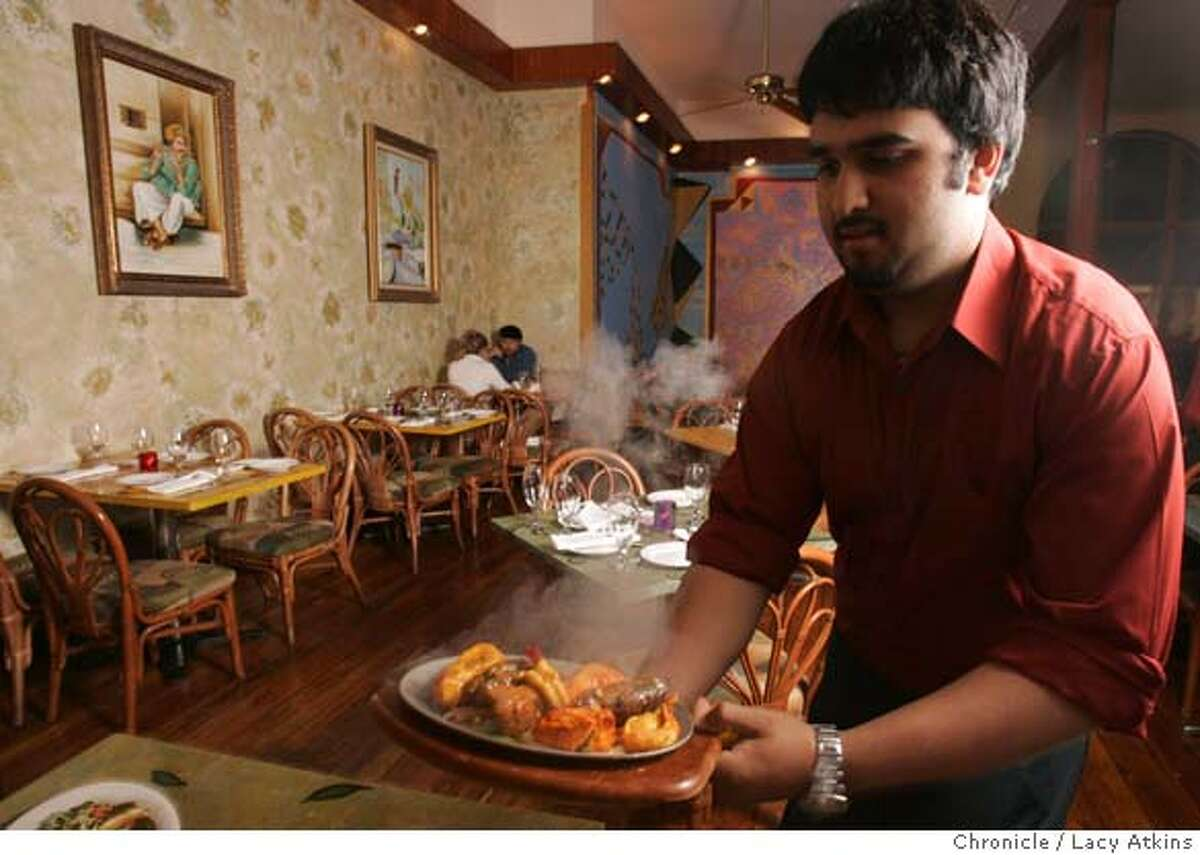Asif Aslam serves up a sizzling dish at the Aslam's Rasoi Restaurant, Tuesday Aug. 15, 2006, in San Francisco. This is an Indian place with a snazzy interior -- colorful walls, handsome wooden floors, decorative tables. Some good, colorful dishes to photograph: Bhindi Masala (okra), murgh masala (chicken curry), goat cheese naan, saag paneer (spinach with fresh cheese). (Lacy Atkins/The Chronicle) Ran on: 08-18-2006 Asif Aslam serves up a sizzling dish at Aslams Rasoi in the Mission District.