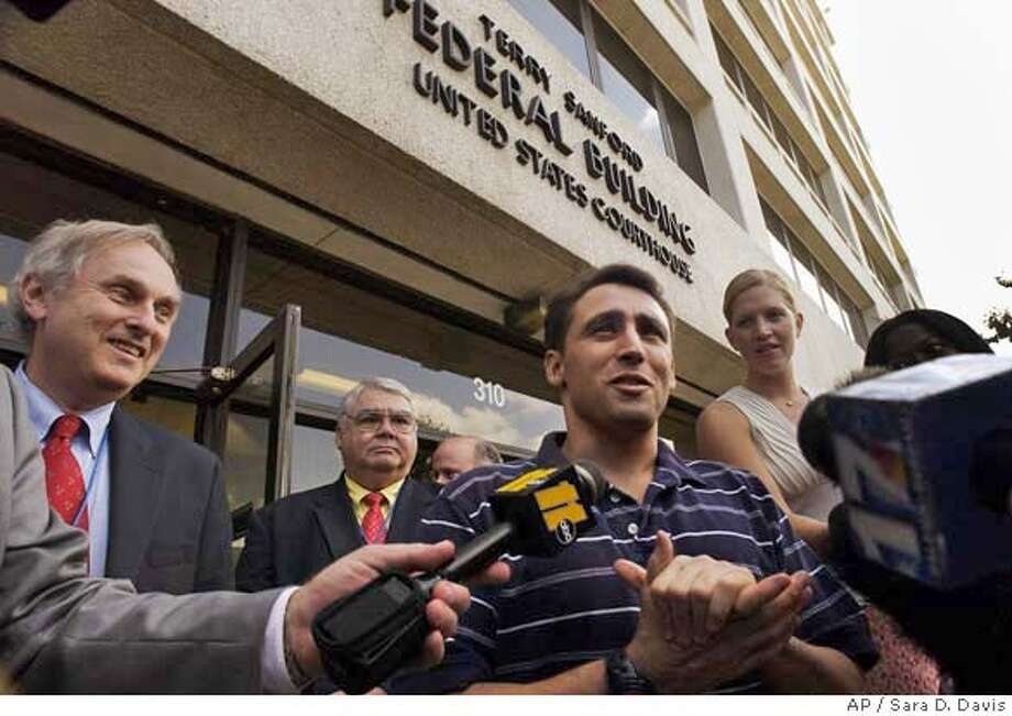 ** ADVANCE FOR WEEKEND AUG. 5-6--FILE ** Former CIA contractor David Passaro 38, center, speaks to the media in front of the North Carolina Federal Building where he was being held in the Wake County jail Friday, in Raleigh, N.C., in this Aug. 27, 2004, file photo. Passaro was released from custody pending a trial for a June 2003 beating of a prisoner in Afghanistan who later died. More than three years later, after several soldiers working at Abu Ghraib have been sentenced to prison, Passaro will finally stand trial when jury selection begins Monday, Aug. 7, 2006. (AP Photo/Sara D. Davis) Photo: SARA D. DAVIS