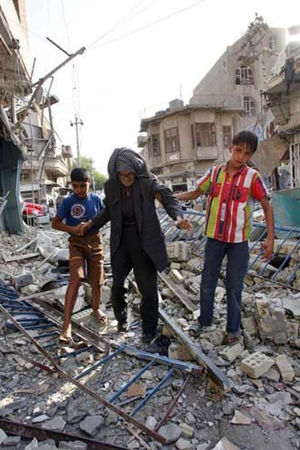 Two Iraqi boys help their grandfather to pass through the rubble from Wednesday's car bomb explosion, in Baghdad, Iraq, Thursday Aug. 17, 2006. Two near simultaneous car bombs exploded in central Baghdad at dusk of Aug. 16, killing 13 people and wounding 55, hours after another bomb killed eight laborers, underlining the increasingly deadly nature of the sectarian strife wracking the capital, police said. Photo: KHALID MOHAMMED
