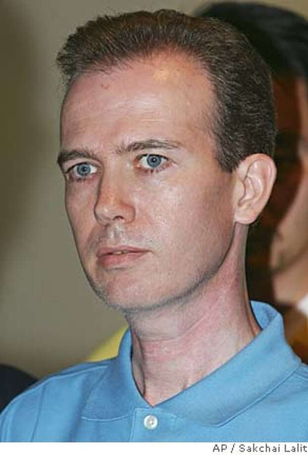 American John Mark Karr is being taken to a police news conference at Immigration office in Bangkok, Thailand Thursday, Aug. 17, 2006. Thai police said that Karr, a 41-year-old American schoolteacher, admitted to the killing a decade ago of 6-year-old beauty queen JonBenet Ramsey in the United States _ a sensational crime some feared would never be solved. Lt. Gen. Suwat Tumrongsiskul, head of Thailand's immigration police, told The Associated Press that John Mark Karr confessed to the killing after his arrest Wednesday afternoon at a downtown Bangkok apartment. (AP Photo/Sakchai Lalit) Photo: SAKCHAI LALIT