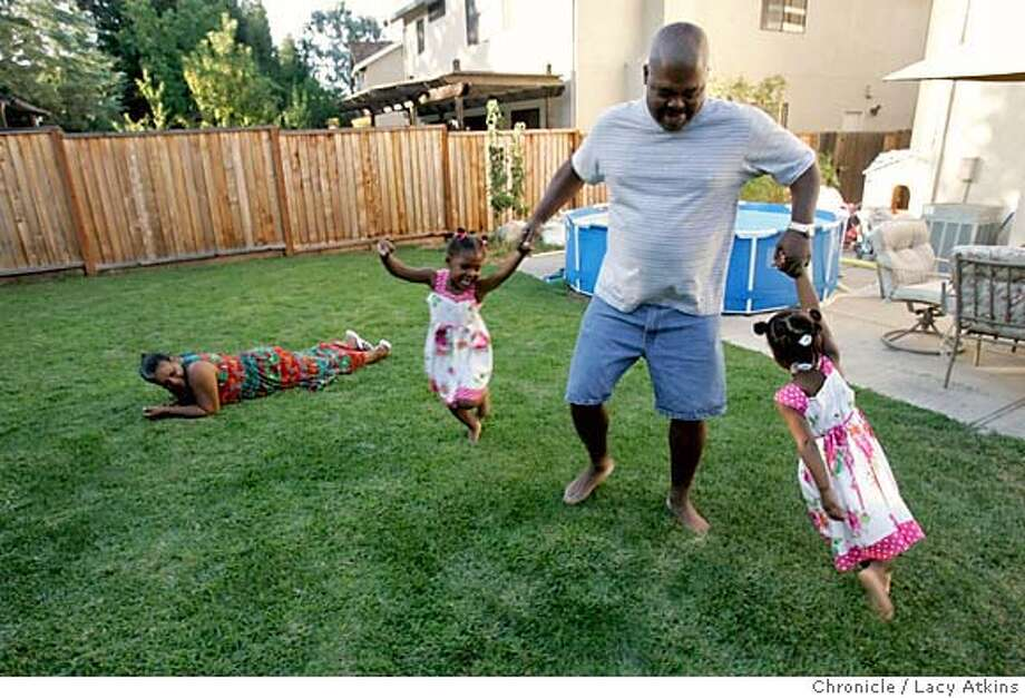 Peter Wilson play with two of his grandchildren (left to right) Keiarra and Aniya, as Yvette watches in the backyard of their home in Antioch, Ca. Sunday Aug. 13, 2006. They sold their victorian home in Berkeley last year to move to a town that has a more home town feeling. His family reflects the trend that suburban cities are growing and becoming younger while cities in the urban core are shrinking and aging. Ca. (Lacy Atkins/The Chronicle) MANDATORY CREDITFOR PHOTGRAPHER AND SAN FRANCISCO CHRONICLE/ -MAGS OUT Photo: Lacy Atkins