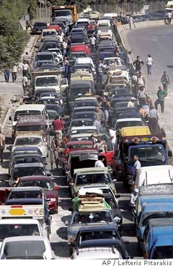 Hundreds of cars with displaced Lebanese returning to southern Lebanon, wait in line to pass a destroyed bridge, attacked by Israeli war planes during the month-long operations, near the town of Zahrani, south of the port city of Sidon, Monday Aug. 14, 2006. Israel halted its offensive against Hezbollah guerrillas as a U.N.-imposed cease-fire went into effect Monday after a month of warfare that killed more than 900 people and devastated much of south Lebanon. (AP Photo/Lefteris Pitarakis) Photo: LEFTERIS PITARAKIS