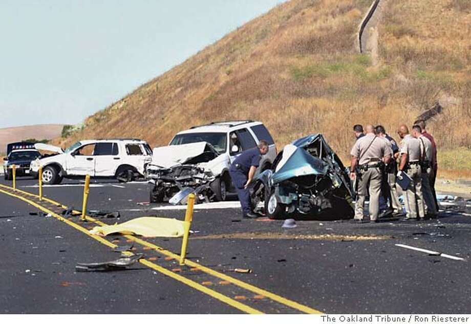 ** CORRECTS SPELLING OF PHOTOGRAPHER'S NAME TO RIESTERER ** California Highway Patrol officers and other law enforcement personnel investigate the scene of a three-vehicle crash that killed four people Monday, Aug. 14, 2006, in Livermore, Calif. A CHP spokesman says one person survived the crash. That person was taken to a hospital with major injuries, according to authorities at the scene. (AP Photo/The Oakland Tribune, Ron Riesterer) ** MANDATORY CREDIT, MAGS OUT, ** MANDATORY CREDIT, MAGS OUT, Photo: RON RIESTERER