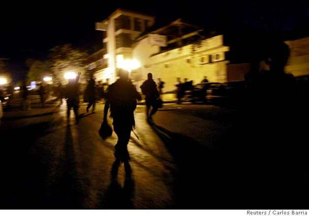 Israeli soldiers walk along an empty street in the northern town of Metula Photo: CARLOS BARRIA