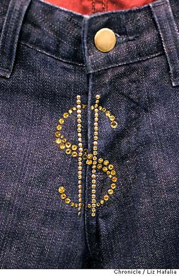 MAGIC05_267_LH.JPG Glitter dollar sign on the fly of Gean Research denim. Photographed by Liz Hafalia on 2/24/06 in Las Vegas, Nevada. SFCRan on: 03-05-2006  Craig Gibson of JH Design Group shows off a $3,000 New York Knicks jacket emblazoned with orange rhinestones. The Bentley, behind, belongs to his boss.Ran on: 03-05-2006 Creditted to the San Francisco Chronicle/ LIZ HAFALIA Photo: Liz Hafalia