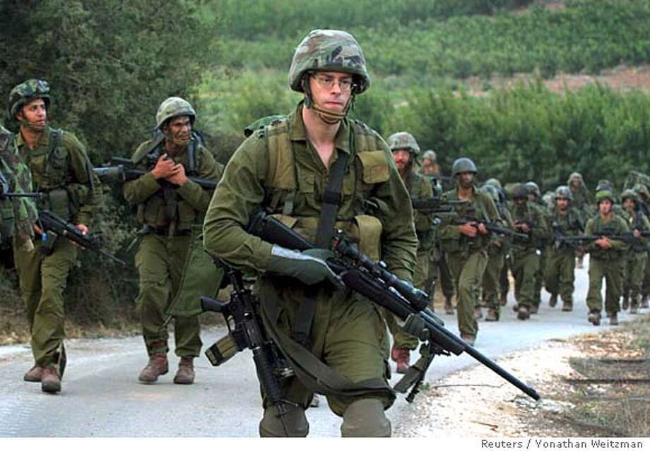 Israeli soldiers walk at the Israel-Lebanon border during a ground operation in northern Israel August 12, 2006. REUTERS/Yonathan Weitzman (ISRAEL) Photo: YONATHAN WEITZMAN