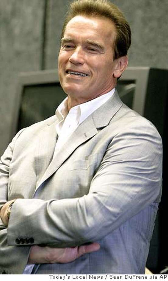 "California Gov. Arnold Schwarzenegger listens to the Carlsbad High School band's rendition of ""Secret Agent Man"" during a visit to the school, Friday, Aug. 11, 2006, in Carlsbad, Calif. Schwarzenegger visited the northern San Diego County school in an effort to highlight the school's arts, music and physical education program, something he says is needed in all California schools. Schwarzenegger has put aside $645 million to fund those kinds of programs. (AP Photo/Today's Local News, Sean DuFrene) ** , MANDATORY CREDIT ** NORTH COUNTY TIMES OUT, , MANDATORY CREDIT Photo: SEAN DUFRENE"