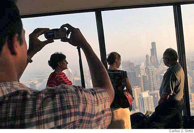 People take photo of each other atop of the John Hancock Situated atop one of the world's tallest buildings, the John Hancock Center, and towering 1,000 feet above the Magnificent Mile, the Signature Room is deservedly famous for its breathtaking vistas. It affords spectacular views from every part of its dining room. Sumptuous Art Deco surroundings complement picture-perfect scenes of the city and Lake Michigan, visible through the floor-to-ceiling windows that circle the room. The food is contemporary American (consider the reasonably priced lunch buffet or the Sunday brunch). Convenient to downtown hotels and shopping, the Signature Lounge is also a popular spot for a romantic rendezvous or business cocktails. Carlos J. Ortiz info@carlosjortiz.com call for more info 312-350-0028 mobile or home 312-738-1241 Photo: Carlos J. Ortiz