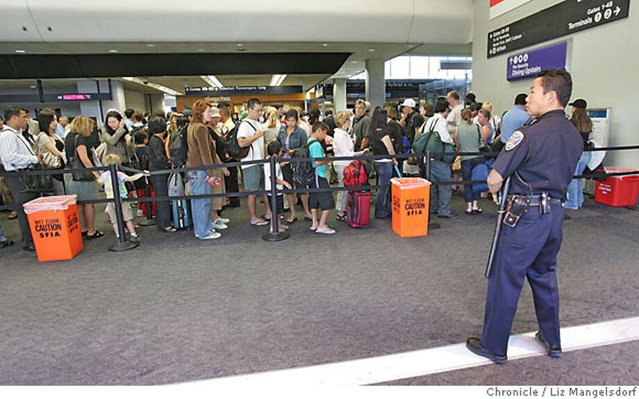 """Series 1 of 2, please compare yesterday photo with today. Officer Alvin Louie airport SFPD over looks the security check point at United Airlines on 8/10. Presently, air traveler lines are moving well compared to yesterday (THIS PHOTO WAS TAKEN 8/10) as the airlines�have brought in more staff in anticipation of the heavier weekend travel. Through the media the word has got out to """"check your liquids"""" or trash them which has forced a heavy flow of checked baggage for the skycaps at curb-side. 8/10/06  {Frederic Larson/The Chronicle} Photo: Frederic Larson"""